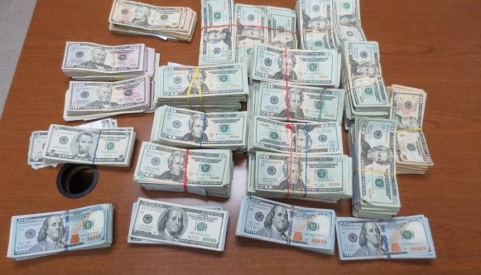 A picture of nearly $150,000 in cash seized by CBP laid out on a table