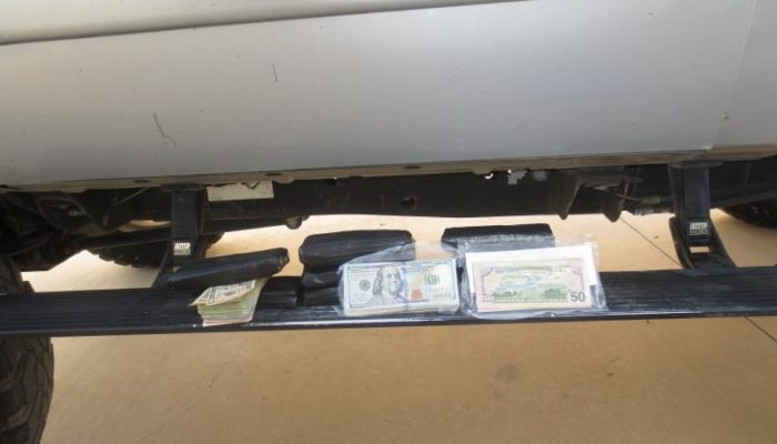 A picture of nearly $70,000 in cash laid out on the body of pick-up truck seized by CBP (U.S. Customs & Border Protection).