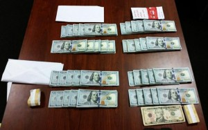 Dulles airport cash seizure showing $40,00 stacked on a table with envelopes