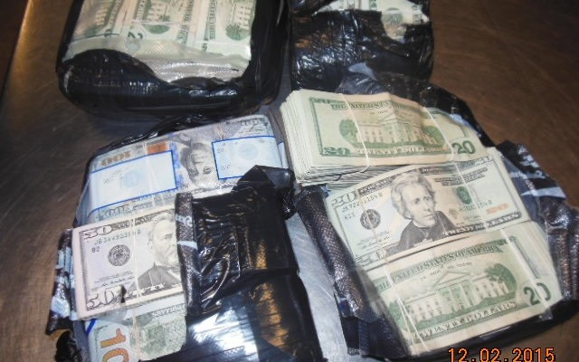 U.S. Currency Seized by CBP Wrapped In Rubber Bands and Black Plastic on a Table