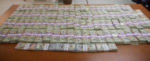 Over $200,000 in cash laid out for presentation on a wooden table as part of the money seizure in Texas by CBP.