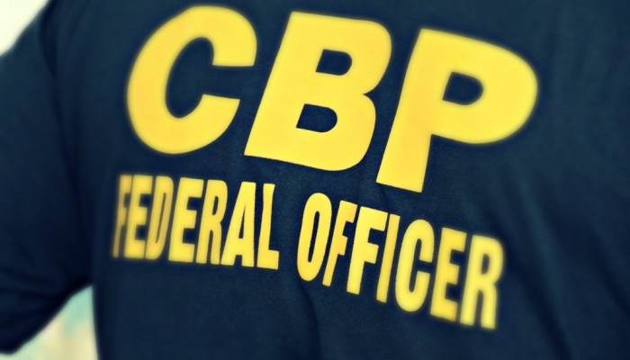 "The back of a CBP officer's shirt reading ""CBP Federal Officer"" in bold yellow letters."