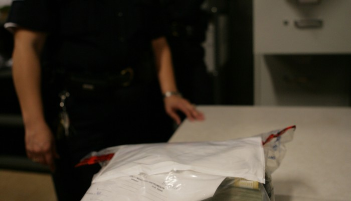 A CBP Officer displays a large bag of seized currency in an evidence bag. Money seizures are a common occurence for CBP.