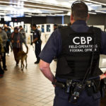 A picture of a CBP officer watching travelers at an airport. CBP Officers at Philadelphia International Airport seized $26,000 from a couple going to Greece for a failure to report the cash