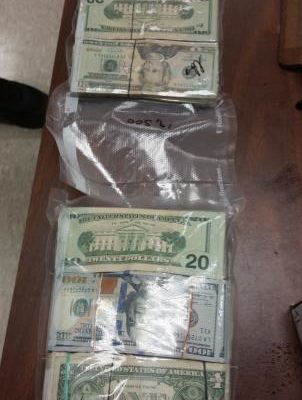 Nearly $60,000 sealed in two clear plastic bags in bundles laying on a table that was confiscated by CBP
