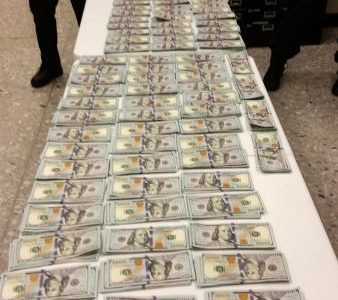 Over $140,000 in cash stacked in piles on a table after seizure by CBP at Dulles airport