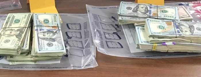 Piles of cash sit atop evidence bags after seizure by U.S. Customs in Brownsville, Texas