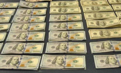$100 bills laid out on table seized by Customs