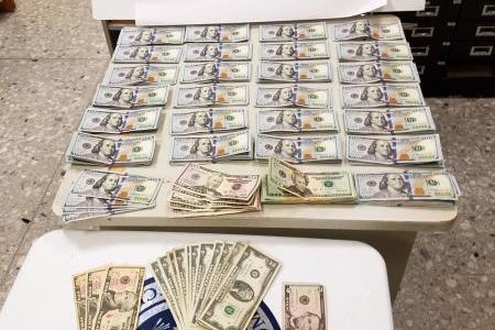 Cash seized by CBP in Dulles airport for failure to report laid out on a table with Homeland Security logo