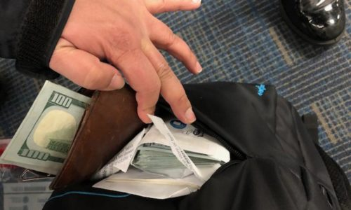 CBP officer revealing $27,500 concealed in a traveler's backpack, seized for bulk cash smuggling and not reporting