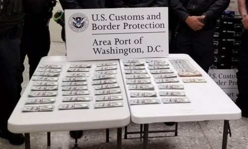 piles of money seized by CBP at dulles airport en route to Netherlands
